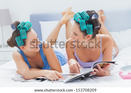 Two friends lying in bed and pointing to magazine at sleepover - stock photo