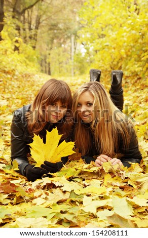 Two friends lying on the autumn leaves - stock photo