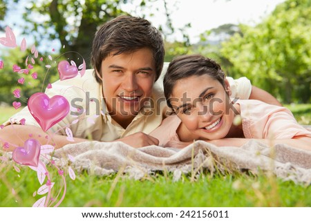 Two friends lying together on a blanket while smiling against valentines heart design