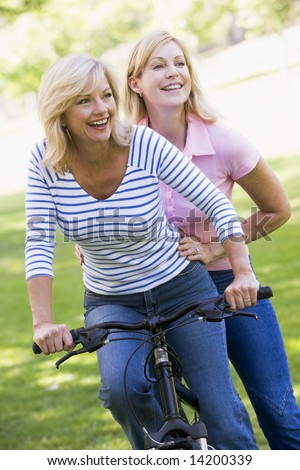 Two friends on one bike outdoors smiling - stock photo