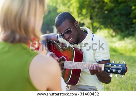 two friends playing guitar and tambourine outdoors - stock photo