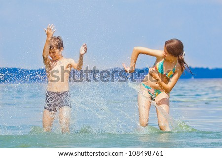 Two friends playing in water, splashing - stock photo