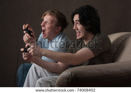 two friends playing video games on gray background
