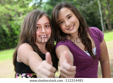 two friends raising his finger at the camera indicating positivism - stock photo