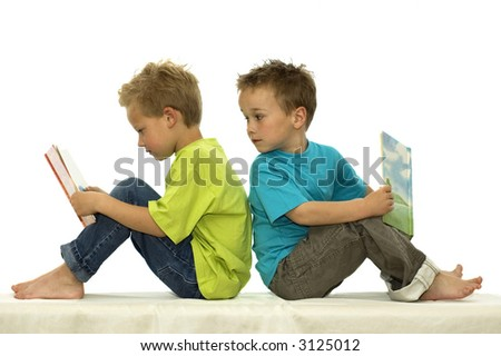 Two friends reading a book, one boy looking surprised at the book of the other. - stock photo