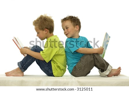 Two friends reading a book, one boy looks at the book of the other, laughing. - stock photo