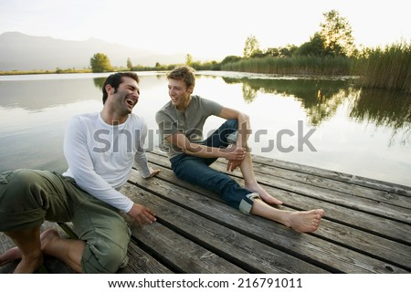 Two friends relaxing on the pier. - stock photo