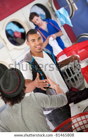 Two friends shake hands in the laundromat - stock photo