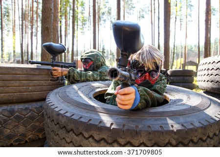 Two friends sitting in big truck tires with paintball guns - stock photo