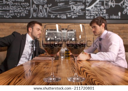 two friends sitting in cafe and eating lunch. two glasses of wine standing on foreground in restaurant