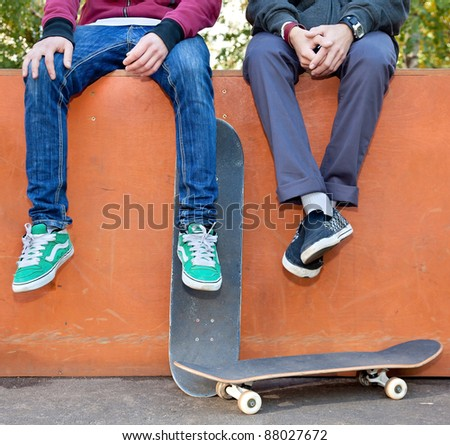 Two friends skateboarders in the skatepark rest after skating - stock photo