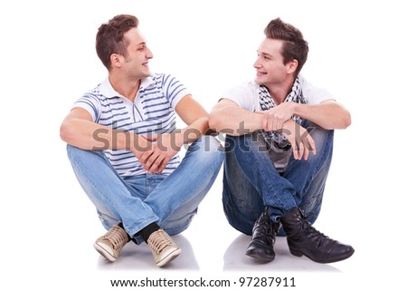 two friends smiling to each other while sitting on a white background - stock photo