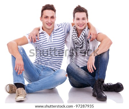 two friends smiling to the camera while sitting on a white background. - stock photo