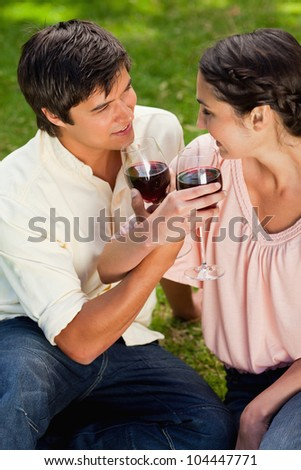 Two friends smiling while they look at each other as they are linking their arms and holding glasses of wine in a park