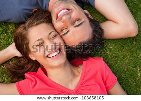 Two friends smiling with their eyes closed while lying head to shoulder with an arm behind their head on the grass