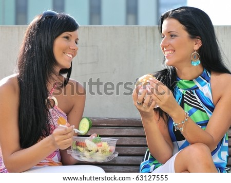 Two friends - smiling young women eating together outdoors on sunny day - stock photo
