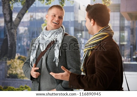 Two friends standing outside of building, chatting, laughing. - stock photo