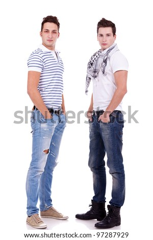 two  friends standing  with their hands in pockets on white background