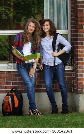 Two friends students standing near a green board in a classroom - stock photo