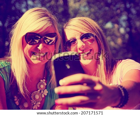 two friends taking a selfie in a park while the sun is setting toned with a retro vintage instagram filter  - stock photo