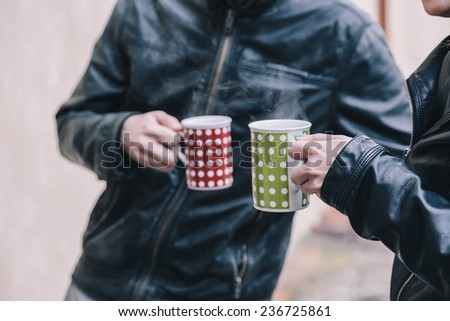 Two friends talk with two cups of hot tea in hand - stock photo