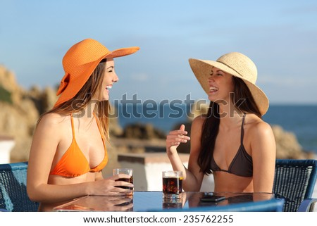 Two friends talking in an hotel terrace on holidays with the beach in the background - stock photo