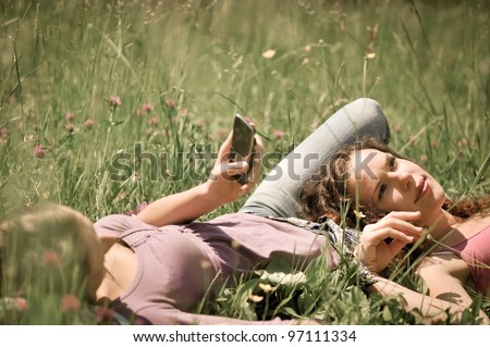 Two friends (teenage girls) relax lying on grass outside in nature - one girl is using cellphone - stock photo