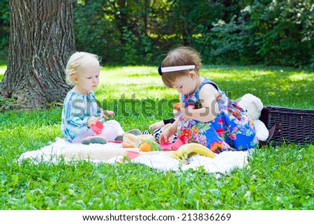 Two friends toddler girls playing in park outdoor sitting on grass on meadow, summer day, childhood lifestyle concept