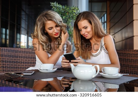 Two friends using phone in outdoor cafe  - stock photo