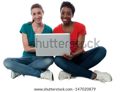 Two friends watching videos on laptop - stock photo