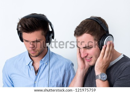 Two friends with headphone listening to music in front of a white background - stock photo