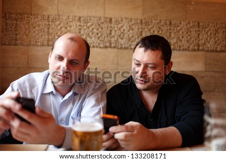 Two friends with mobile phones are in a pub - stock photo