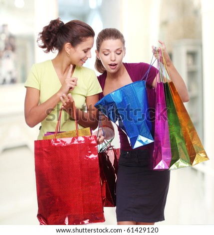 Two friends with shopping. One girl wonders purchases second girl - stock photo