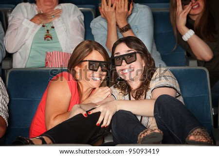 Two frightened women with 3D glasses get close together - stock photo