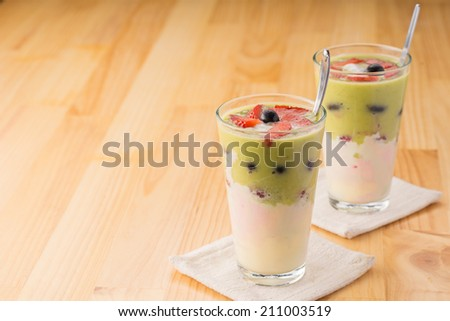 Two fruit and berry desserts in tall glasses - stock photo