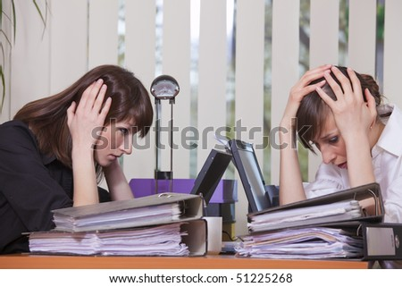 two frustrated businesswomen by work in the office - stock photo