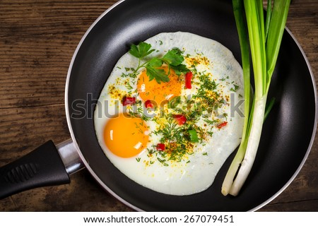 two frying eggs with greens in pan on wooden table - stock photo