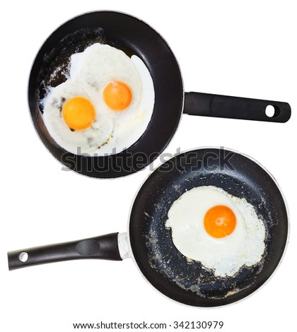 two frypans with one and two fried eggs isolated on white background - stock photo