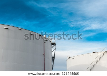 Two fuel storage tanks with a blue sky