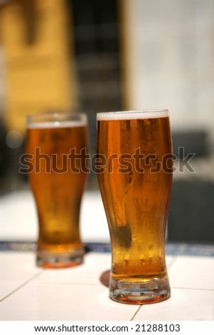 two full beer glass with bubbles on table
