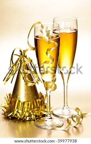 Two full champagne flutes with party hat and ribbons - stock photo