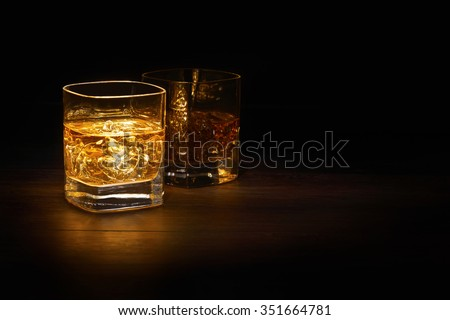 Two full glasses of Single Malt Whiskey on a wooden table top. - stock photo