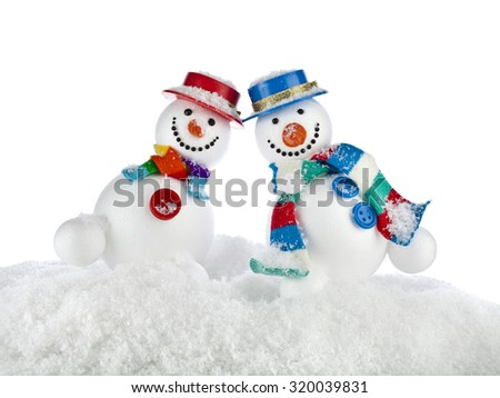 Two fun dancing snowman in a striped scarfs, mittens and cylinder hat isolated on white background - stock photo