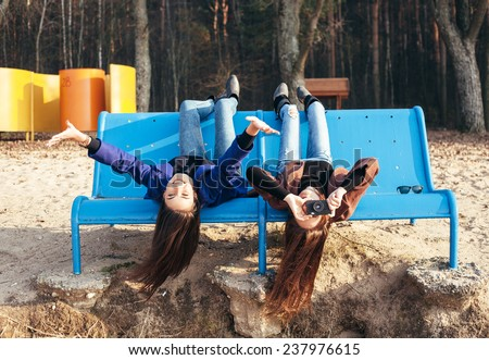 Two funky friends having fun and taking photos lying upside down on a bench on the beach. Outdoor lifestyle portrait - stock photo