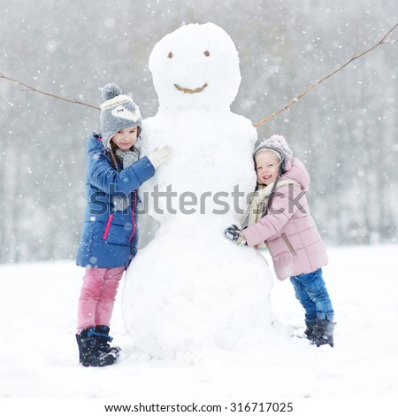 Two funny adorable little sisters building a snowman together in beautiful winter park during snowfall - stock photo