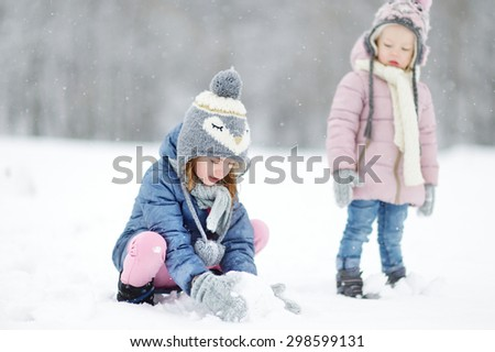 Two funny adorable little sisters making a snowman together in beautiful winter park during snowfall - stock photo