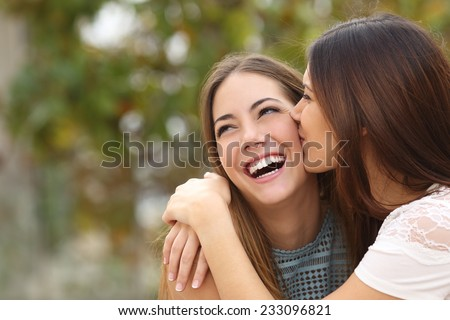 Two funny affectionate women friends laughing and kissing outdoors - stock photo