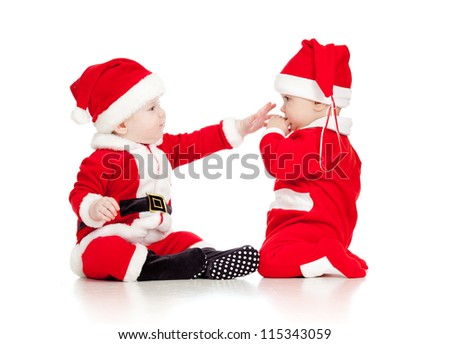 two funny babies in Santa Claus clothes play together isolated on white background - stock photo