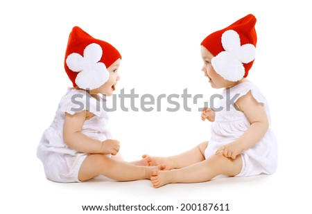 Two funny baby twins in hats sitting face to face - stock photo