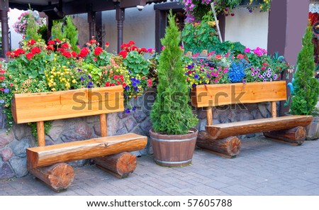 Two funny benches over stone wall and flowers.